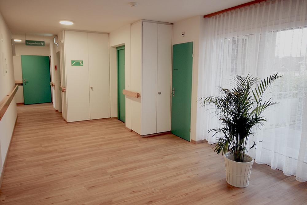 Helle Räumlichkeiten im Pflegeheim. Ansicht Gang im Obergeschoss mit Hinweisen