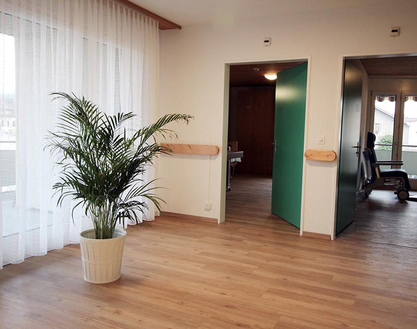 Helle Räumlichkeiten im Pflegeheim. Zugang Einbettzimmer mit Balkon und Therapieraum